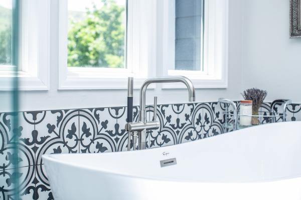 Freestanding bathtub and black and white tile