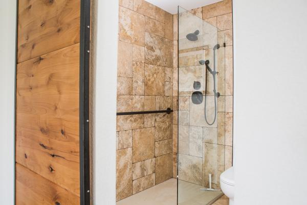 Traditional travertine tile bathroom with barn door