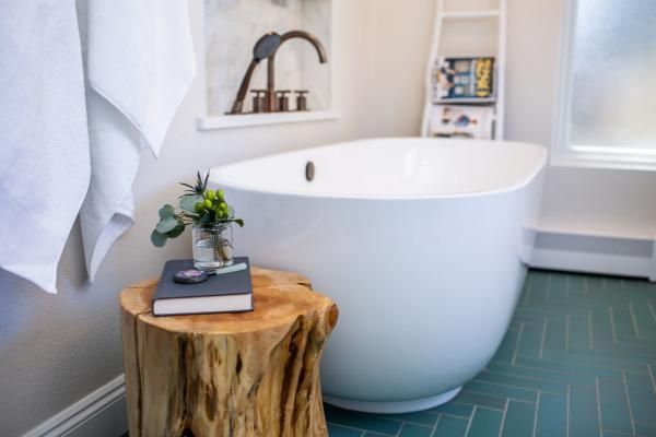 White freestanding tub next to log table