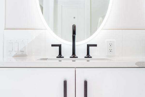 Backlit mirror and white cabinet