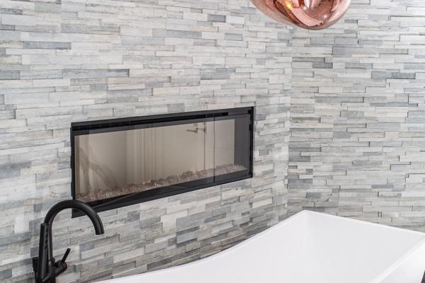 Freestanding tub in front of fireplace