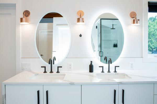 White vanity with copper sconces