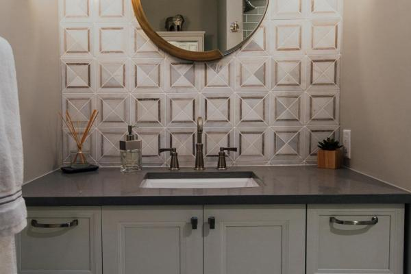 Floating bathroom vanity with marble backsplash