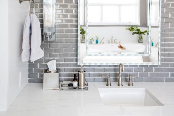 Gray brick backsplash and silver mirror