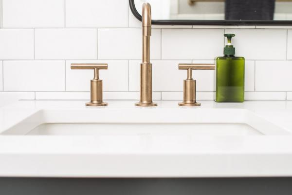 Detail of gray cabinet and brass faucet
