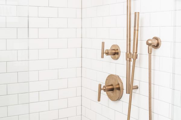 Brass shower fixture and white subway tile