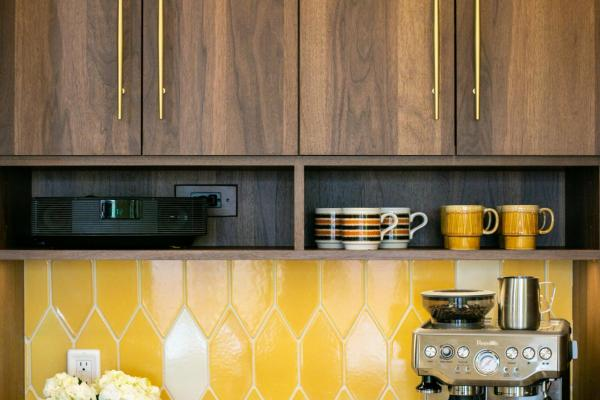 detail of walnut cabinets and yellow backsplash