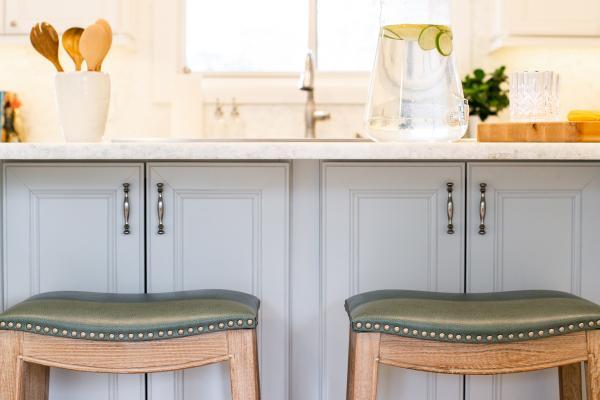 detail of stools set under countertop overhang at island