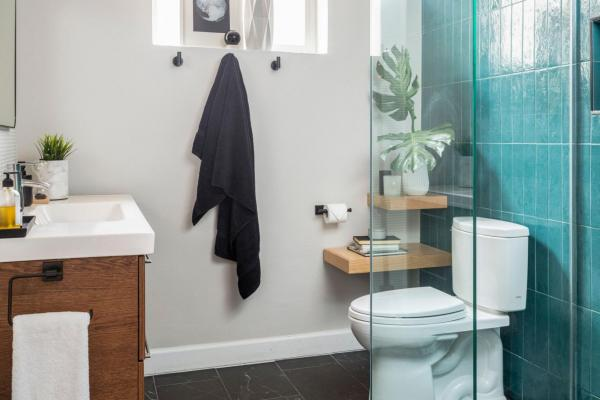 Bathroom with black floor and teal wall tile
