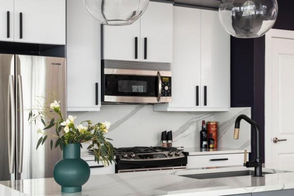 Modern kitchen with gray cabinets and glass pendants